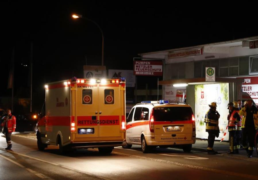 German emergency services workers work in the area where a man with an axe attacked passengers on a