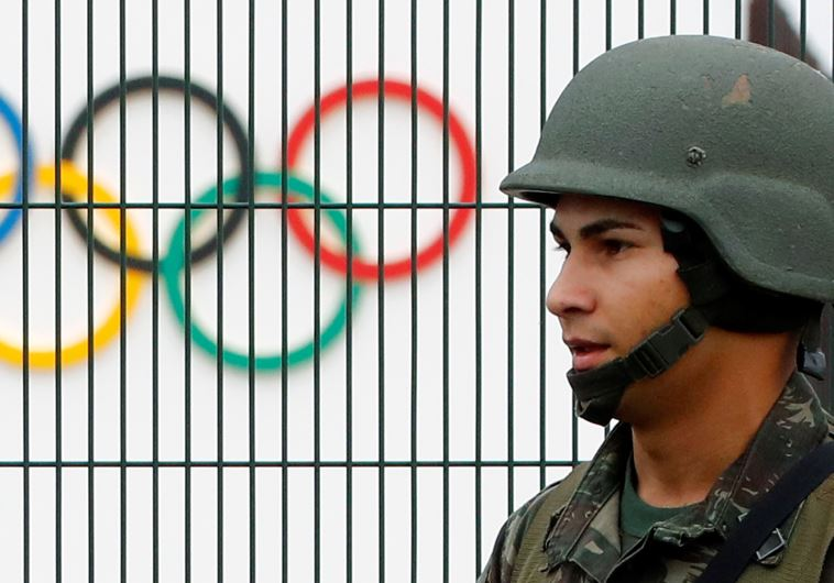 A Brazilian military police soldier patrols at the security fence outside the 2016 Rio Olympics Park