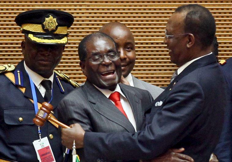 Zimbabwe's President Robert Mugabe (C) talks to Chad's President Idriss Deby (R) after the opening c