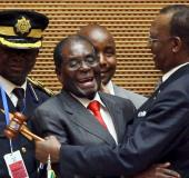 Zimbabwe's President Robert Mugabe (C) talks to Chad's President Idriss Deby (R) after the opening c