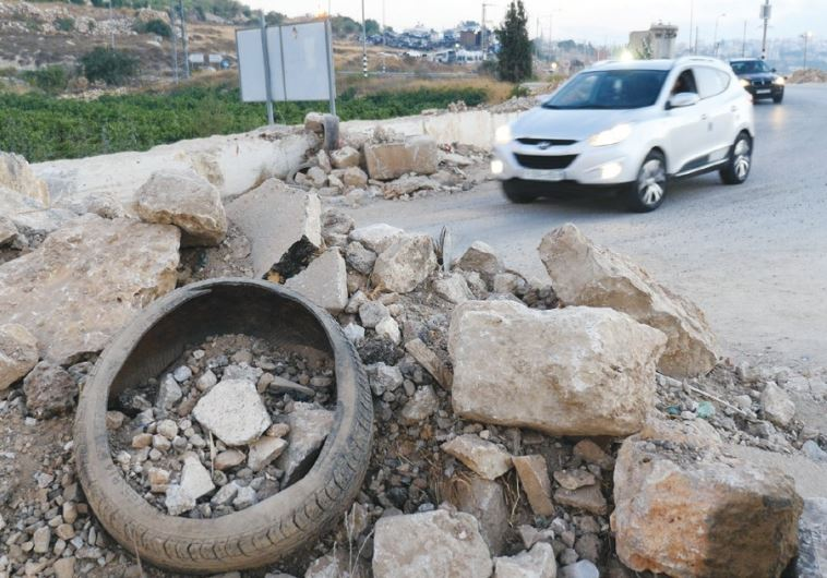 A MOUND OF EARTH is piled up to serve as a roadblock outside Sa'ir village yesterday. (