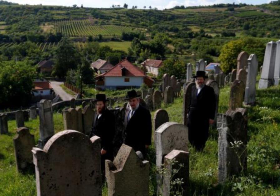 Three rabbis, the sons and grandson of a leading Hasidic rabbi Eliezer Ehrenreich walk in the cemet