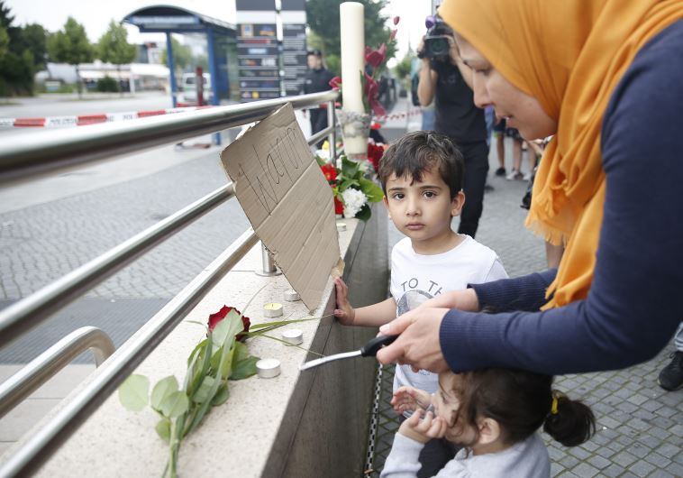 Woman lights a candle at scene of Munich shooting