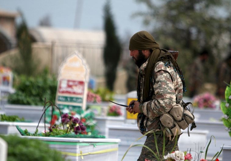 A Kurdish People's Protection Units (YPG) fighter walks near graves of fellow fighters during a visi