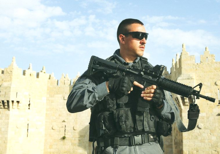 A BORDER POLICE officer patrols the area outside the Damascus Gate of Jerusalem's Old City recently.