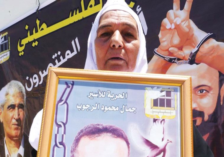 YASMIN RAJOUB displays a photo of her son, Jamal, who is serving a life sentence for terrorism at Ri