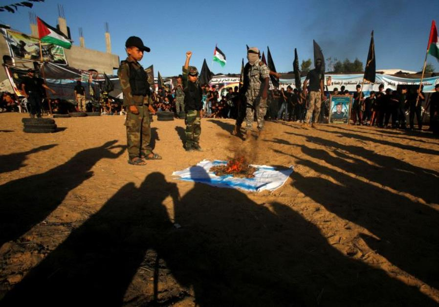 Palestinians burn an Israeli flag during a military-style graduation ceremony at a summer camp organ