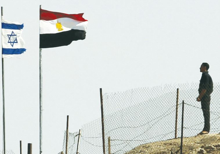 EGYPTIAN AND ISRAELI flags flutter next to each other at the Taba border crossing.