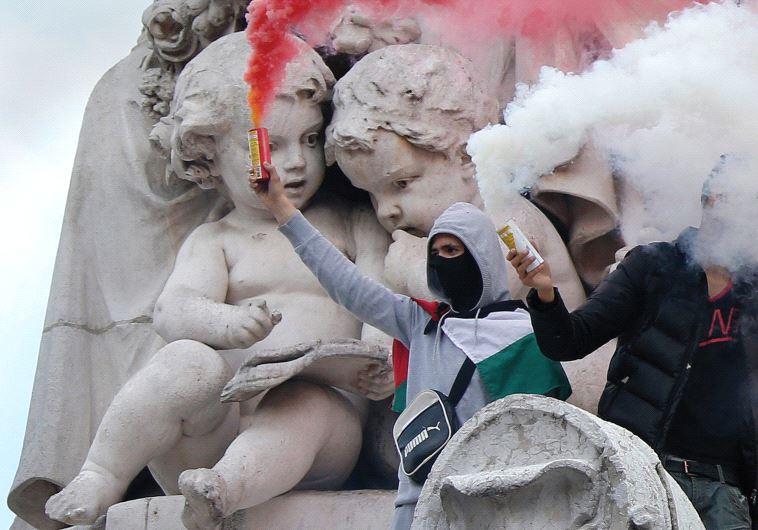 Protesters climb on the statue in the Place de la République in Paris during a banned demonstration
