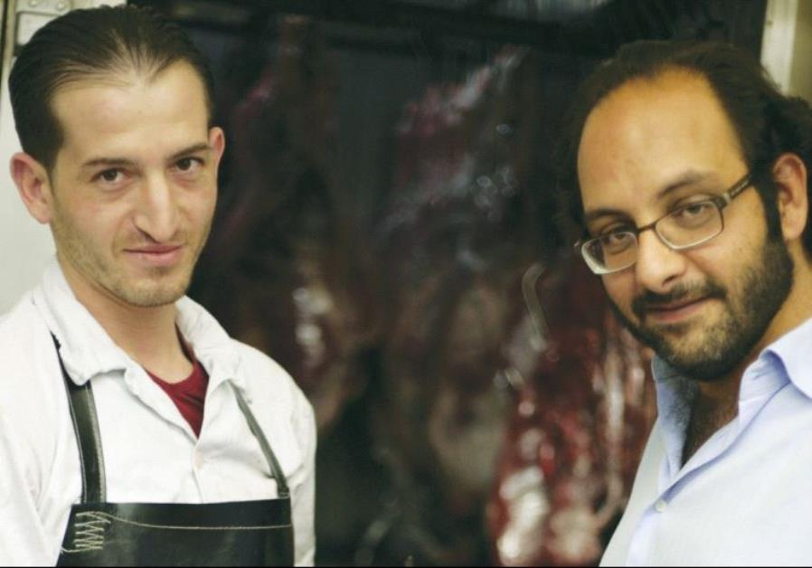 FADI KATTAN (right) makes a purchase from his butcher last week for his Hosh al-Syrian guest house i