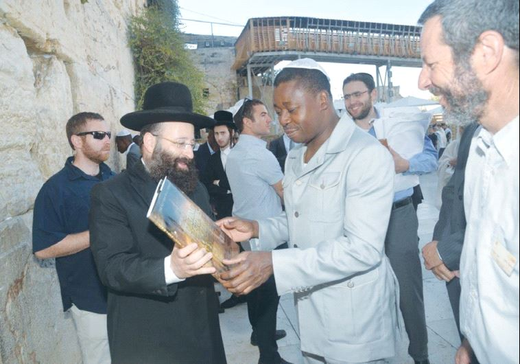 TOGO PRESIDENT Faure Gnassingbe receives a book from Rabbi Shmuel Rabinowitz during a visit to the W