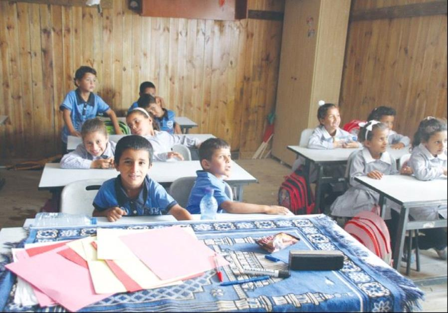 CHILDREN SIT at a Beduin school in al Khan al Amar in the West Bank yesterday. The school is slated