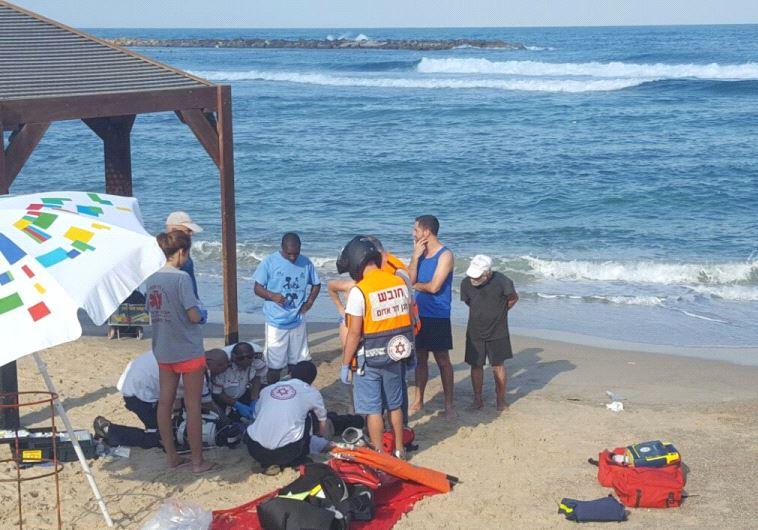 Magen David Adom paramedics treating a man on Tel Aviv's Hilton Beach.