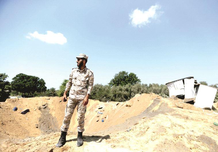 Un agent de sécurité du Hamas examine un cratère après la frappe israélienne