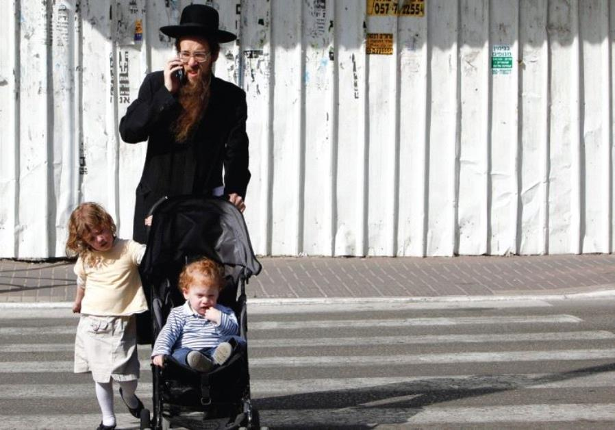 A MAN and his children cross the street in Bnei Brak while he speaks on his cellphone.