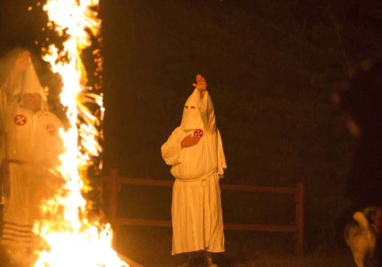 A member of the Ku Klux Klan salutes a lit cross during a cross lighting ceremony