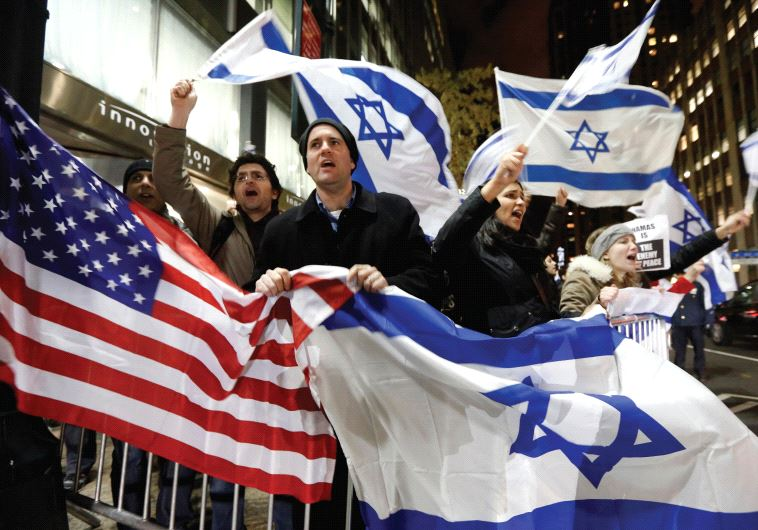 People wave American and Israeli flags