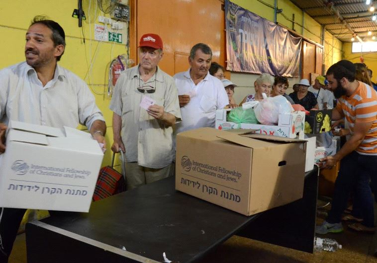 People receive IFCJ food packages prior to Rosh Hashana at the Yad B'Yad warehouse in Lod.