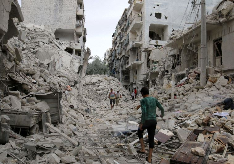 People inspect a damaged site after airstrikes on the rebel held Tariq al-Bab neighbourhood of Alepp