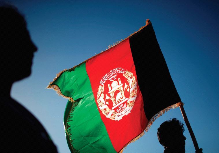 A MAN holds an Afghan flag, one of several that have the words 'God is great' on them