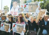 RELATIVES AND ACTIVISTS hold pictures of assassinated Jordanian Christian writer Nahed Hattar yester