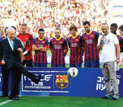 SHIMON PERES kicks a soccer ball to Barcelona superstar Lionel Messi (right) during the Spanish club