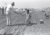 THEN-PRIME MINISTER Shimon Peres greets a young Nahal Brigade soldier working in the field at a sett