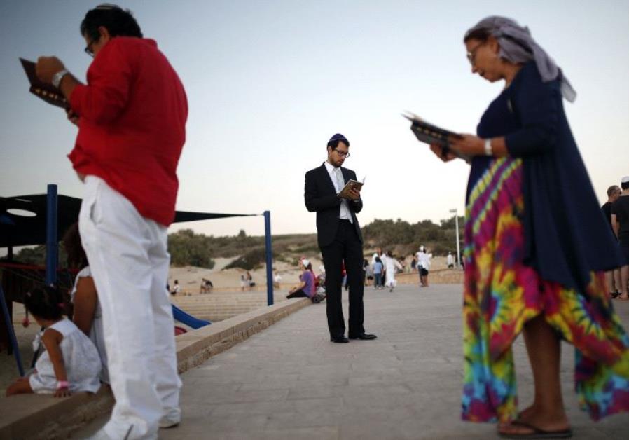 Jews take part in the Tashlich prayer, a Rosh Hashanah ritual, on the shores of the Mediterranean Se