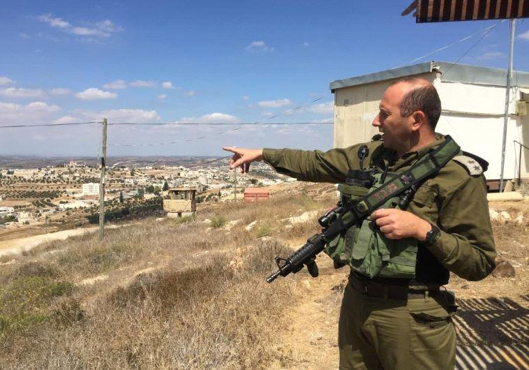 Lt Col Tsafrir Harshoshanim points at Palestinian villages west of Hebron