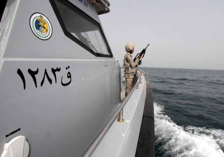 A Saudi border guard watches as he stands in a boat off the coast of the Red Sea on Saudi Arabia's m