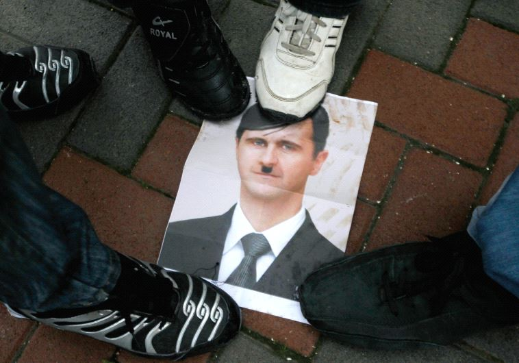 PROTESTERS STEP on a picture depicting Syria's President Bashar al-Assad as Hitler during a protest