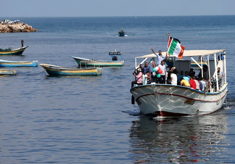 Palestinians ride a boat as they take part in a rally to show solidarity with Gaza-bound flotilla Oc