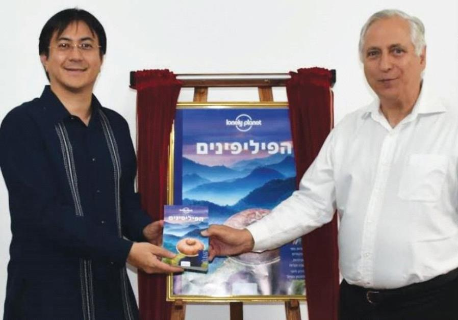 FILIPINO AMBASSADOR Neal Imperial (left) presents a Hebrew edition of the Lonely Planet Philippines