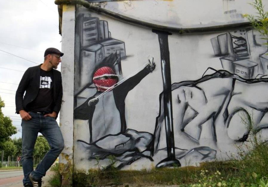 Teacher Christoph Glanz stands next to Palestinian slingshot graffiti.