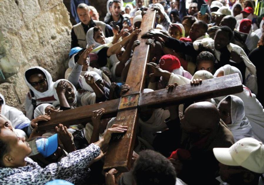 ETHIOPIAN CHRISTIAN worshipers carry a cross during a procession along Via Dolorosa