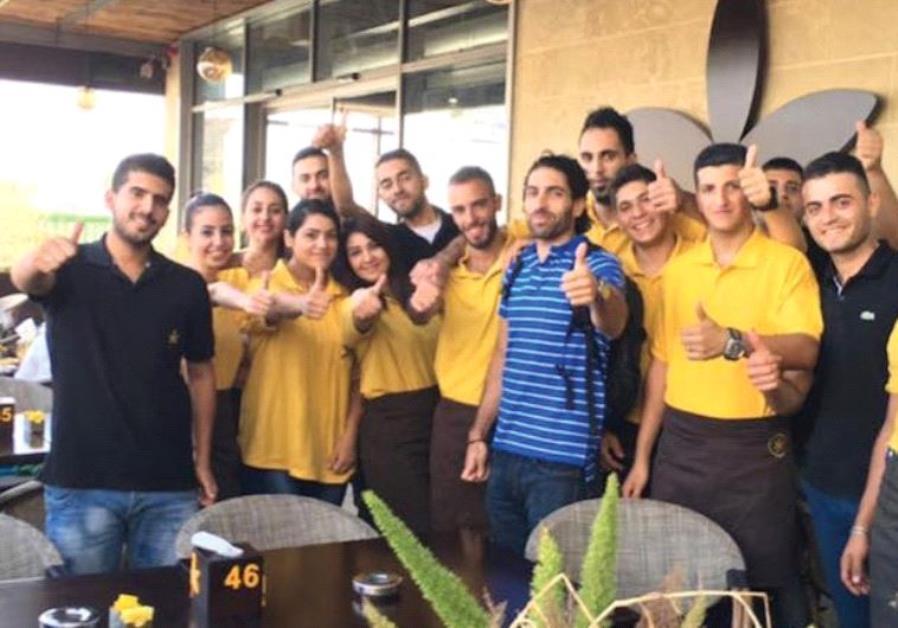 OWNER JOHN SAADEN posing with members of his staff outside Jasmine Cafe in Nablus.