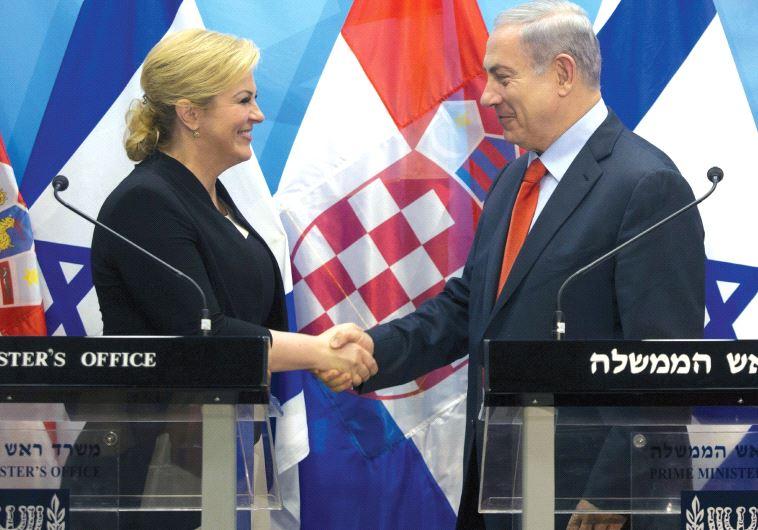 PRIME MINISTER Benjamin Netanyahu and Croatian President Kolinda Grabar-Kitarovic shake hands during