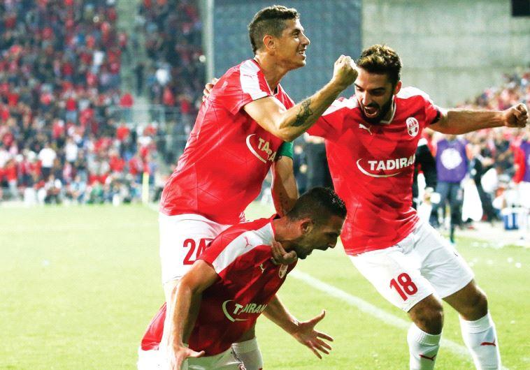 Hapoel Beersheba striker Ben Sahar (kneeling) celebrates with teammates Michael Ohana (right) and Ma