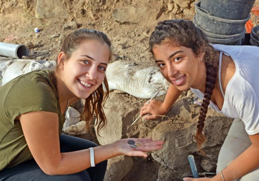 Dor Yogev and Ella Dicks hold coins discovered in the town of Kama