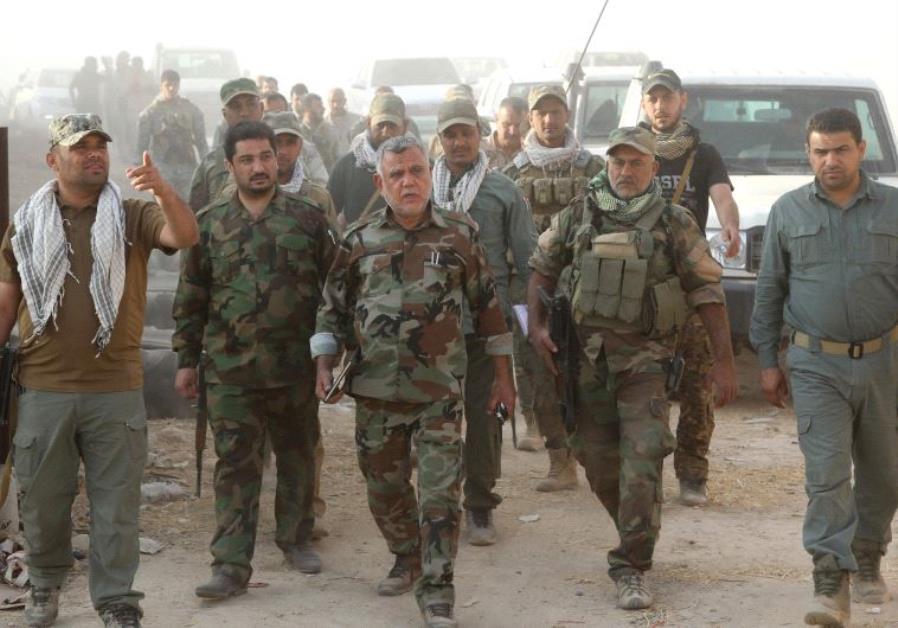 HADI AL-AMARI (center) the head of the pro-Iranian Badr Organization walks with Shi'ite fighters sou