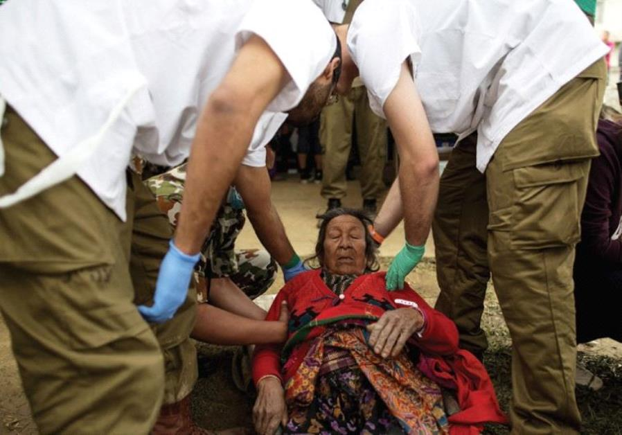DOCTORS HELP an injured resident at the IDF field hospital in Kathmandu in 2015.
