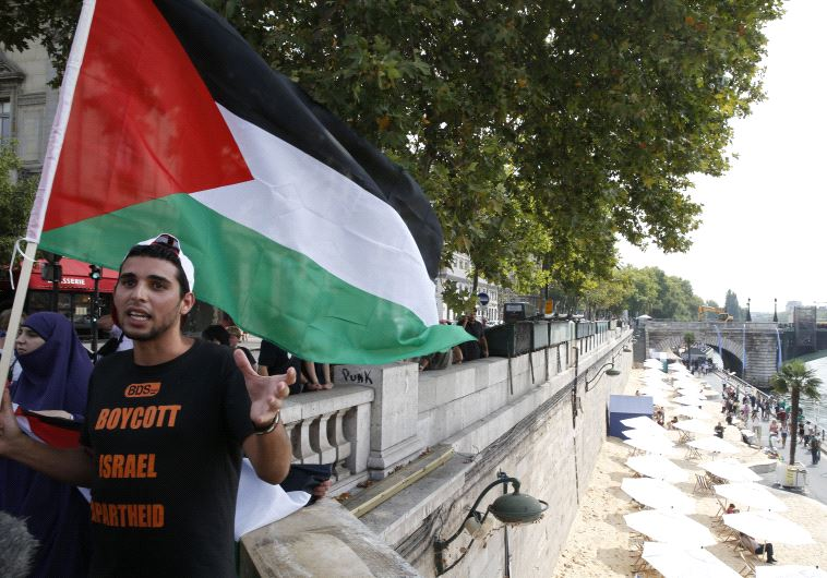 "A man wearng a T-shirt with the message, ""Boycott Israel Apartheid"" holds a Palestinian flag during"
