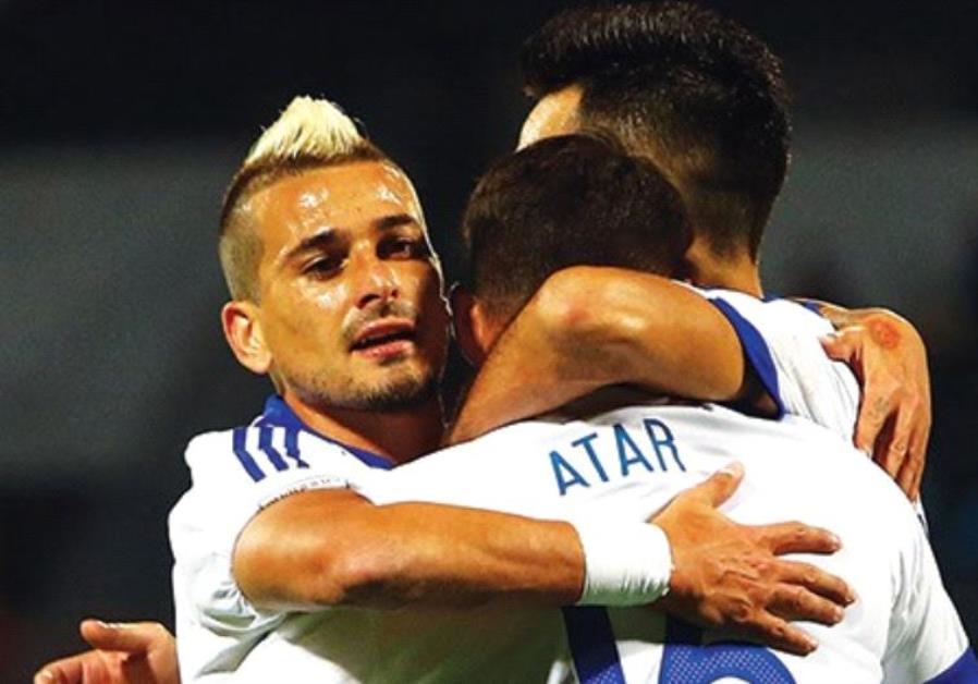 Israel national team midfielders Maor Buzaglo (left) and Eran Zahavi embrace striker Eliran Atar (ce