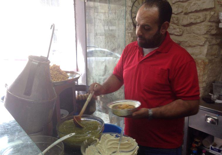 An Employee of Bandali prepares hummus