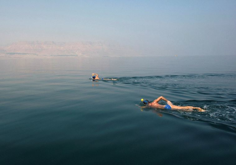ENVIRONMENTAL ACTIVISTS take part in the Dead Sea Swim Challenge, swimming on Tuesday from the Jorda
