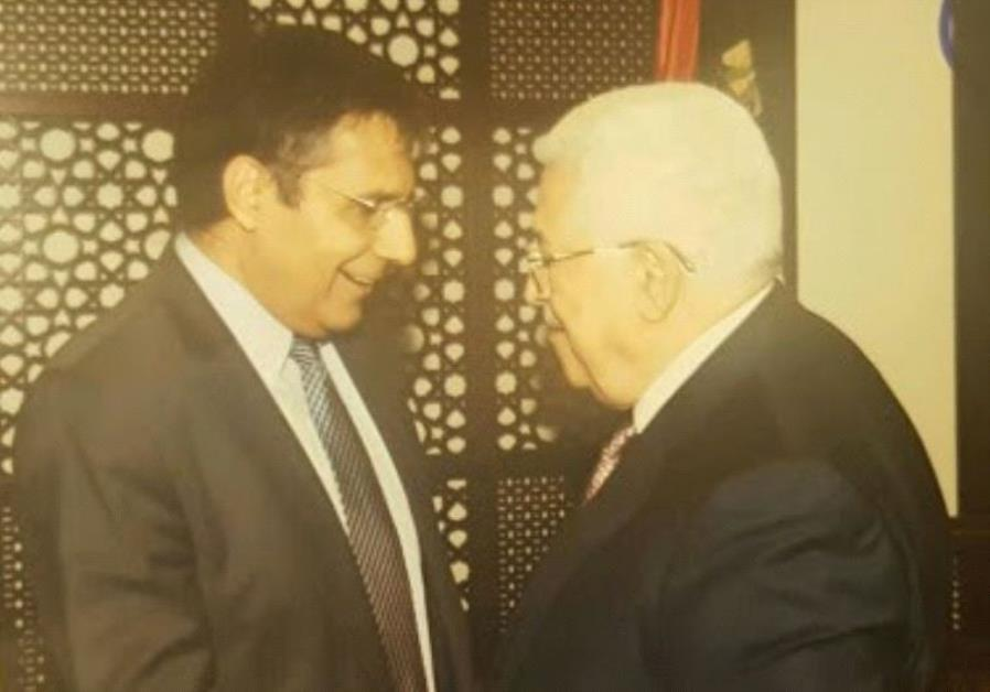 Zionist Union MK Yossi Yona and PA President Mahmoud Abbas shake hands in the Mukata in Ramallah.