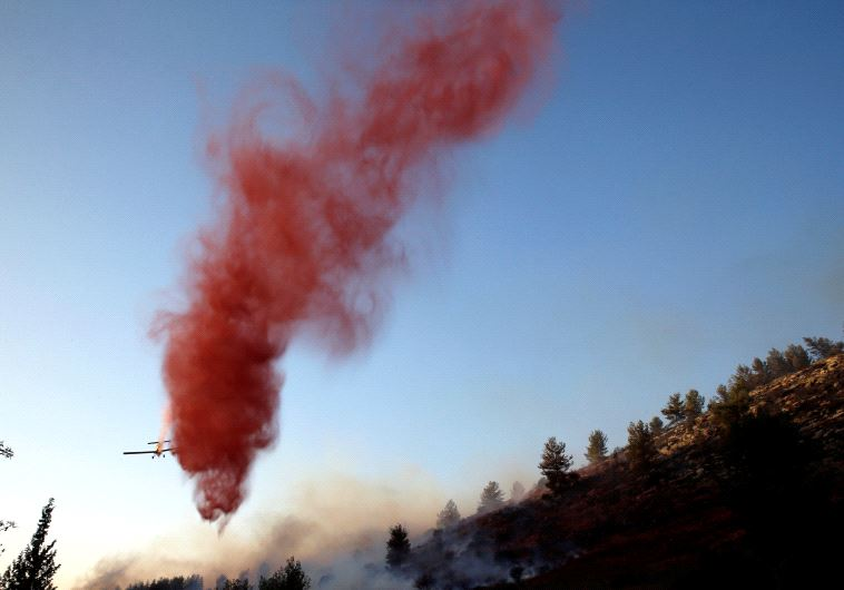 A firefighting plane drops fire retardant during a wildfire, near the communal settlement of Nataf, close to Jerusalem November 23, 2016. (REUTERS/Ronen Zvulun)