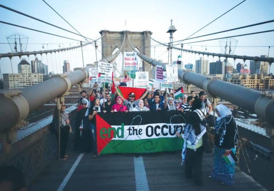 DEMONSTRATORS SHOUT pro-Palestinian slogans as they march across the Brooklyn Bridge during a pro-Pa
