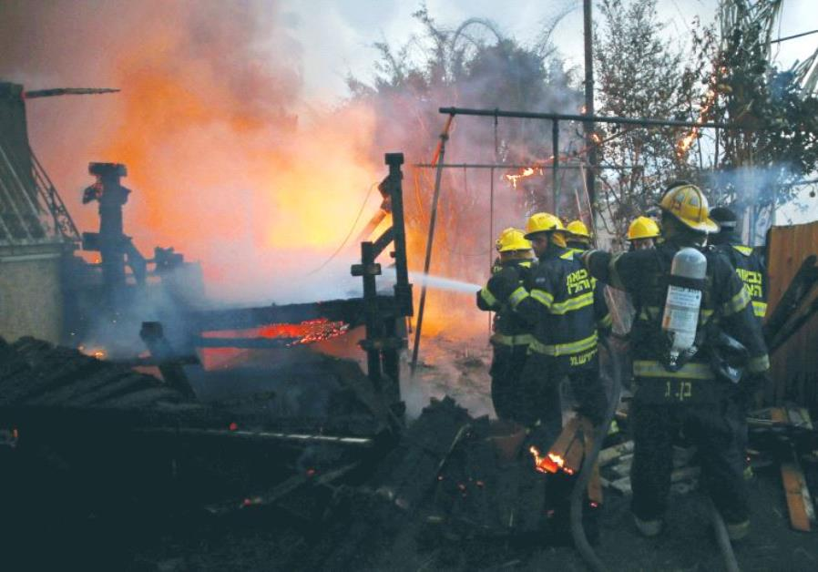 Fire-fighters work to extinguish a fire in Haifa.