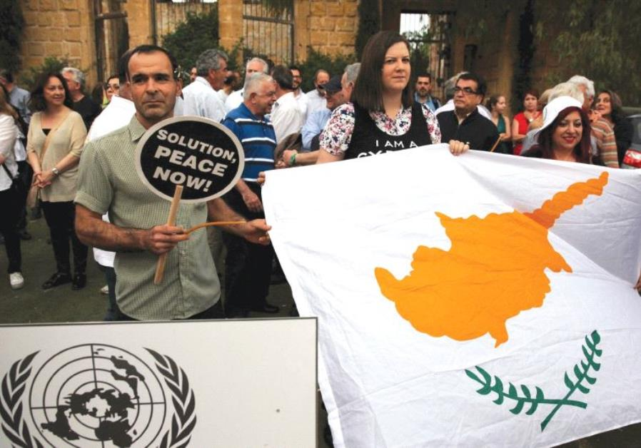 PROTESTORS HOLD a Cyprus flag during a demonstration in favor of a peace settlement on divided Cypru